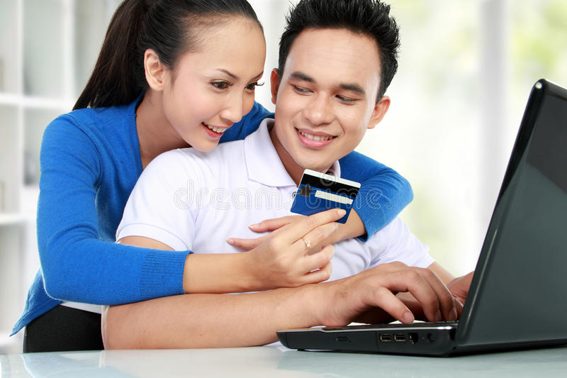 Happy couple shopping online. Portrait of happy couple shopping online using credit card royalty free stock images