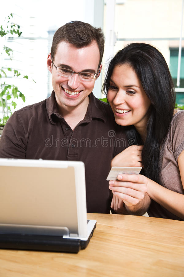 Happy couple shopping online. A happy couple holding a credit card shopping online royalty free stock images