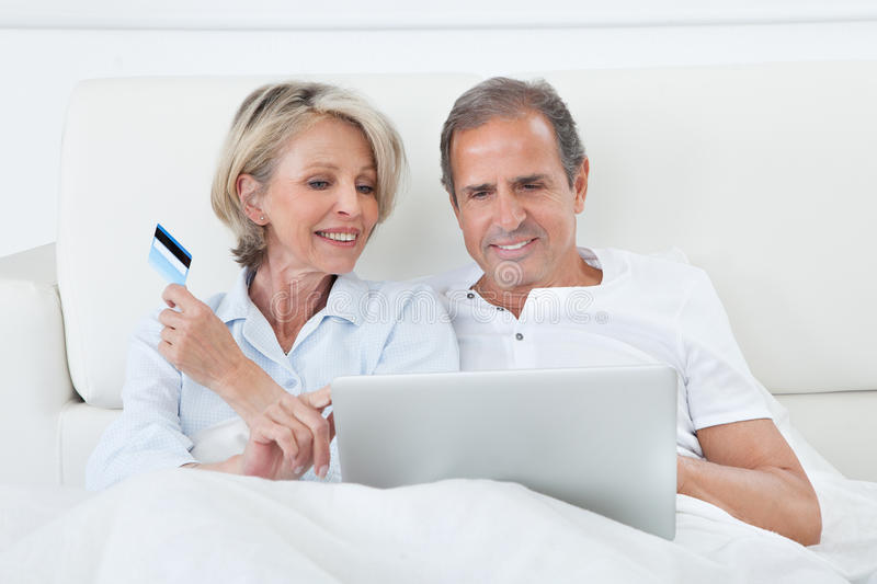 Happy couple shopping online. Couple In Bedroom Shopping Online Holding Credit Card stock photos