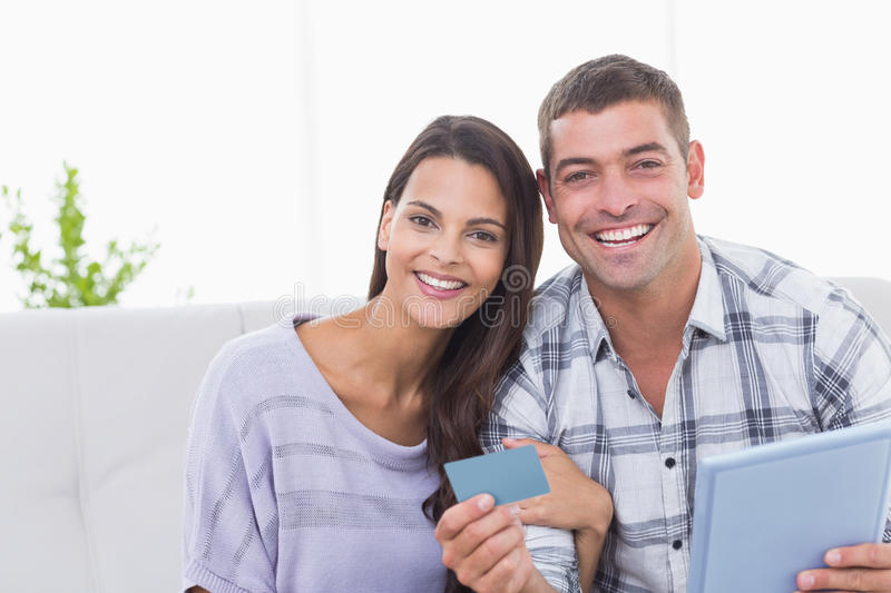 Happy couple shopping online on digital tablet using credit card. Portrait of happy couple shopping online on digital tablet using credit card at home royalty free stock photos