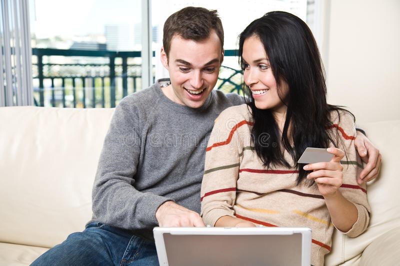 Happy couple shopping online from home. A happy couple holding a credit card shopping online from home stock photography