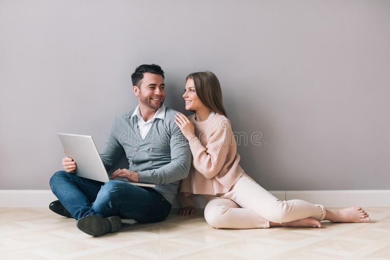 Happy couple shopping online on laptop while sitting floor. stock photo
