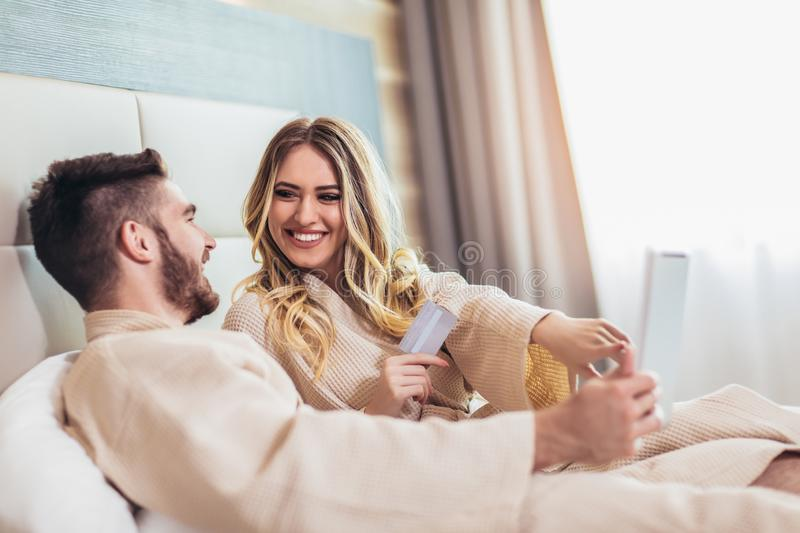 Happy couple shopping online in luxury hotel room royalty free stock images