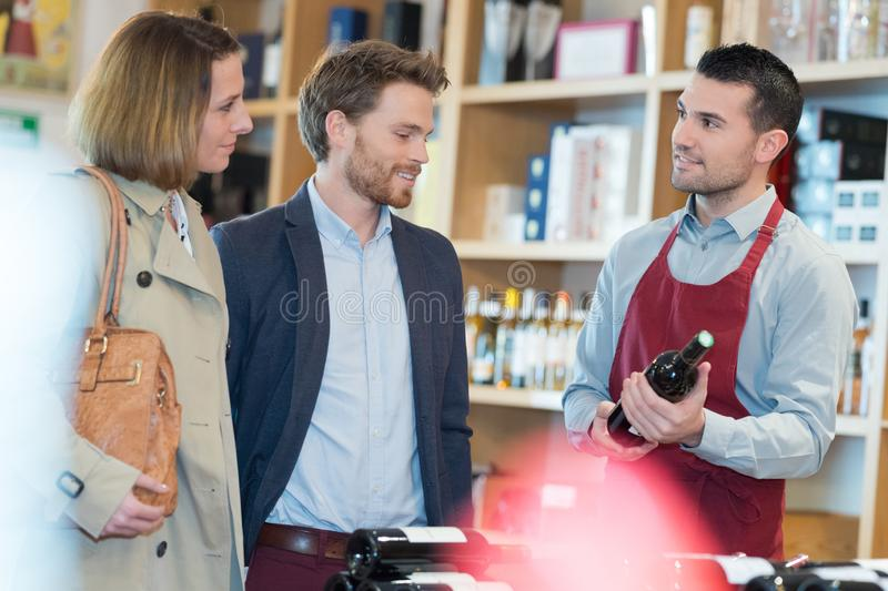 Happy couple shopping in supermarket buying wines royalty free stock image