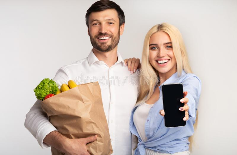 Happy Couple Showing Cellphone Screen Holding Shopping Bag, White Background royalty free stock photography