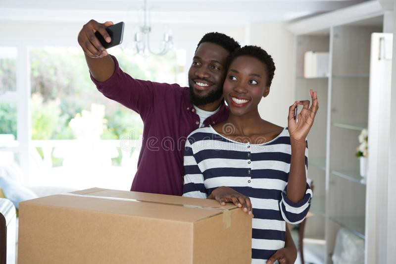 Couple showing house key while taking selfie with mobile phone. Happy couple showing house key while taking selfie with mobile phone stock image