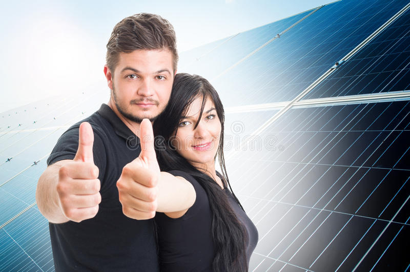 Happy couple showing like on solar power photovoltaic panel back royalty free stock photos