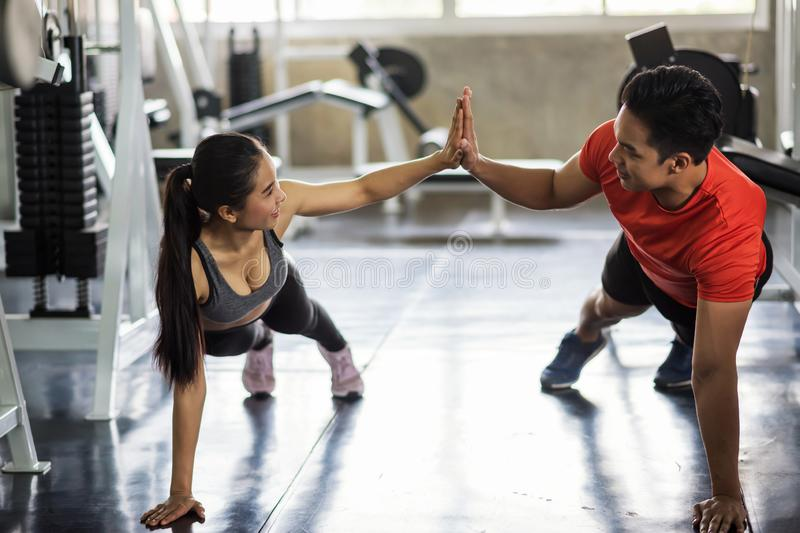 Happy couple sit up in gym. Young Asian sweet couple sit up exercise together at gym. Happy fitness men and women giving each other a high five during work out royalty free stock images