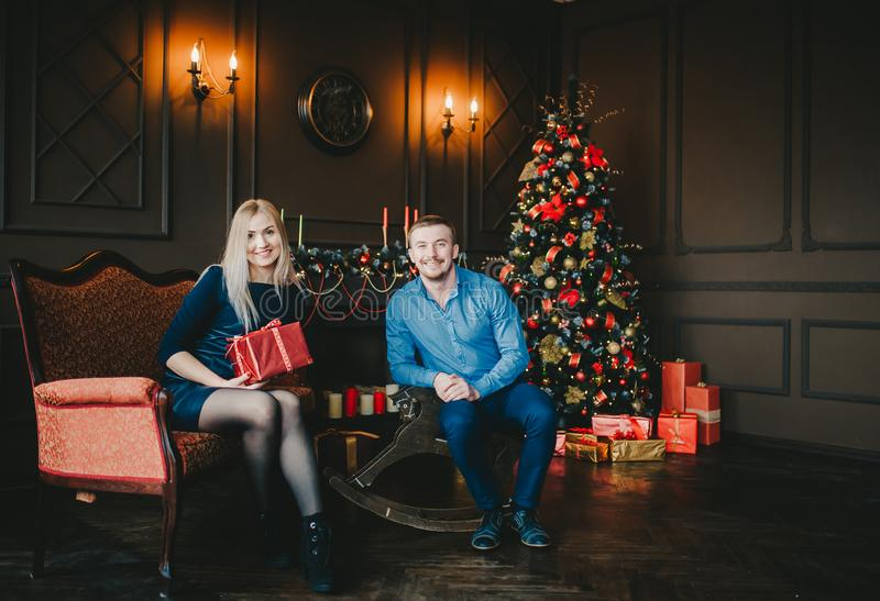 Happy couple sitting by a Christmas tree in a cozy dark living room on Christmas eve royalty free stock photos