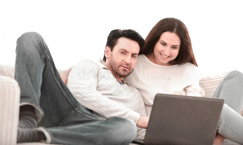 Happy couple sitting on the couch in her arms, looking at laptop royalty free stock photography