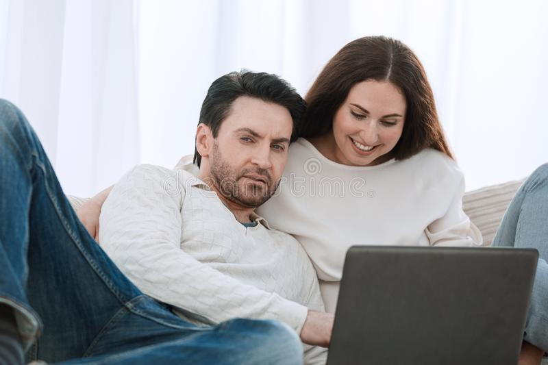 Happy couple sitting on the couch in her arms, looking at laptop royalty free stock photo