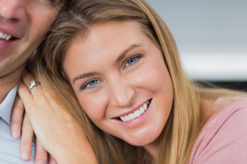 Download Happy Couple Sitting On The Couch Smiling At Camera Focus On Wom Stock Photo - Image: 33052160