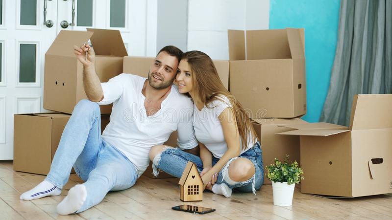Happy couple sitting on floor in new house. Young man give keys to his girlfriend and kissing her. Happy couple sitting on floor in new house. Young men give stock image