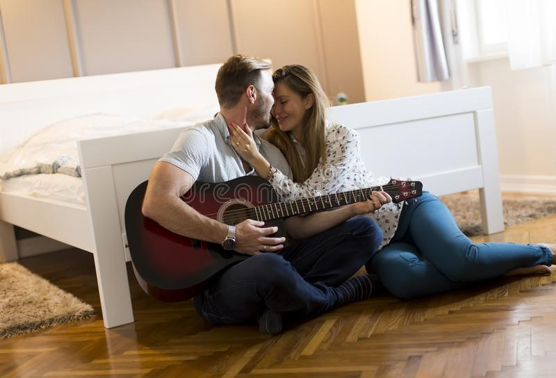 Happy couple sitting on the floor with guitar. Happy couple sitting on the floor in the room with guitar royalty free stock photos