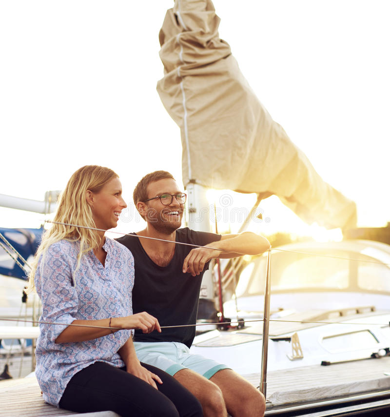 Happy Couple Sitting On Sandy Beach Embracing Kissing: Happy Couple In Front Of Yacht Stock Photo