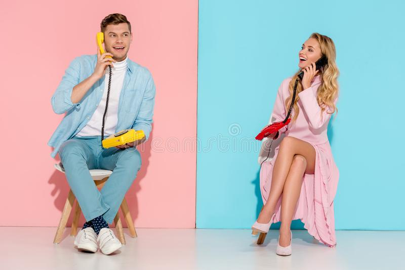 Happy couple sitting and having conversation on vintage telephones. With pink and blue background stock image