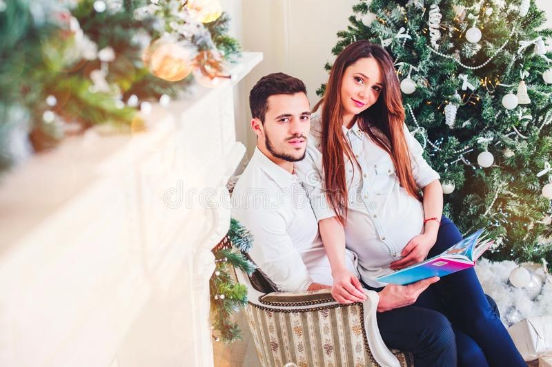 Happy couple sitting in the living room having Christmas book, behind the decorated Xmas tree, the light give a cozy atmosphere. New Year and xmas theme stock photos