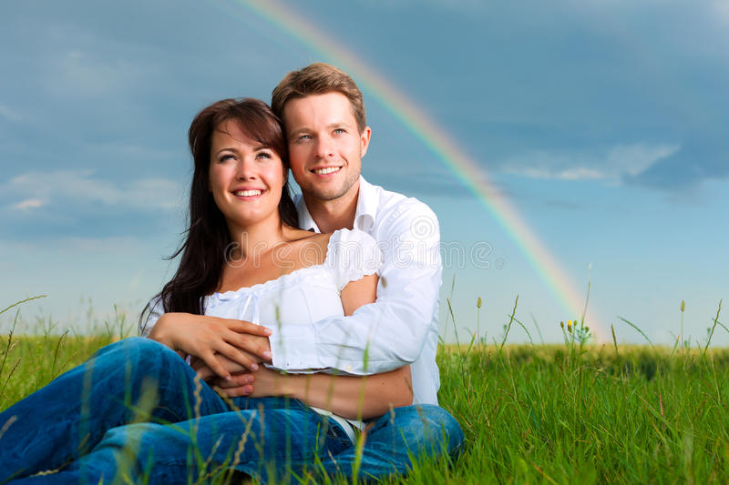 Happy couple sitting on a meadow under rainbow royalty free stock photography