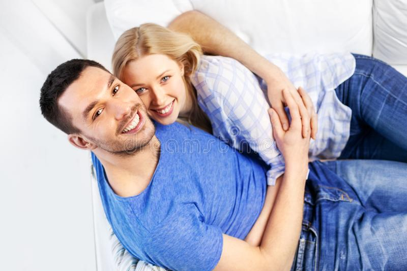 Happy couple sitting on sofa and hugging at home stock photography