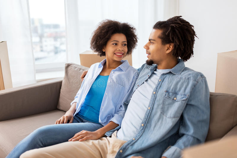 Happy couple sitting on sofa and talking at home stock photography
