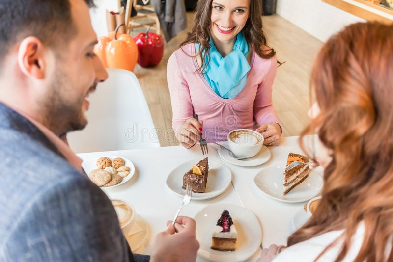 Happy couple sitting at table with their mutual friend in a tren stock image