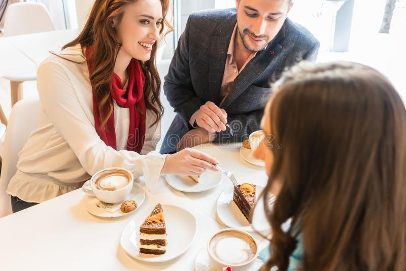 Happy couple sitting at table with their mutual friend in a trendy cafe royalty free stock photo