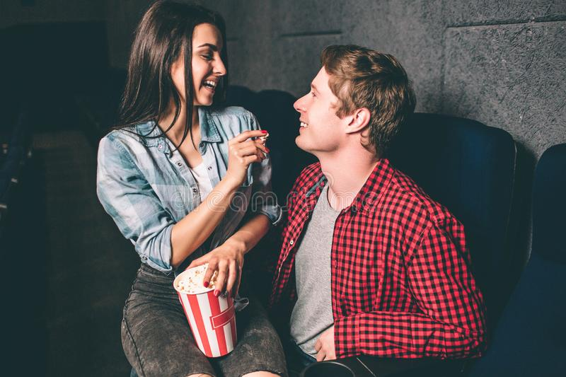 Happy couple is sitting together and smiling to each other. Girl is holding a piece of popcorn in one hand and a small stock image