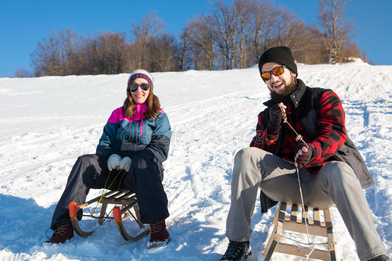 Happy couple sledding down the hill. Happy young couple sledding down the hill stock photo