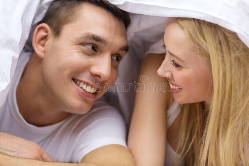 Happy couple sleeping in bed stock photos