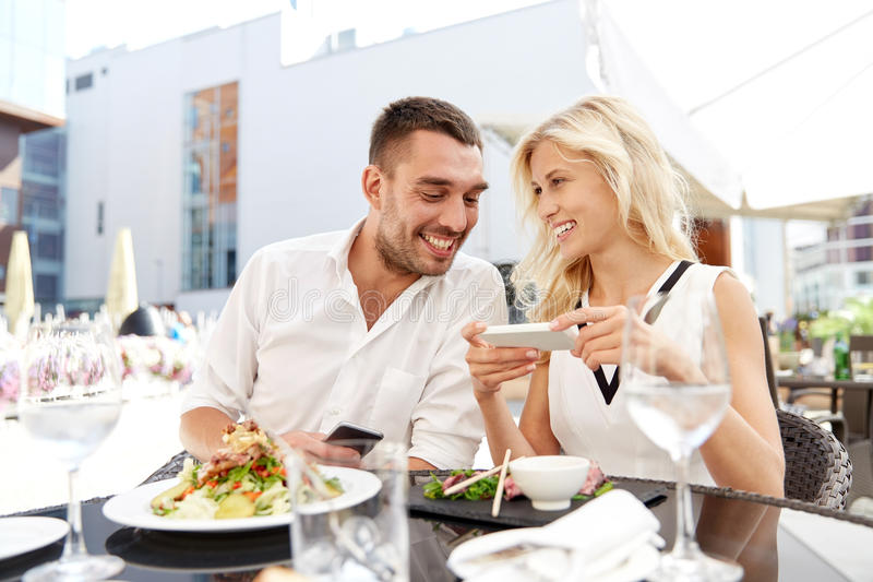 Happy couple with smatphone at restaurant terrace. Love, date, technology, people and relations concept - smiling happy couple with smatphone at restaurant royalty free stock photo
