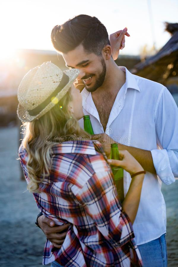 Happy couple smiling and drinking beer at beach royalty free stock photo