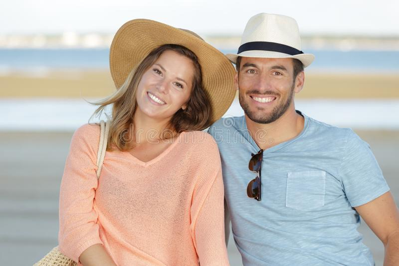 Happy couple smiling at each other at beach stock images
