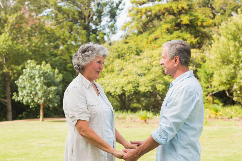 Happy couple smiling and facing each other royalty free stock photography