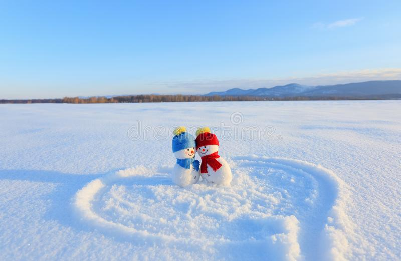 Happy couple of smiling snowman. Blue red hat and scarf. Painted heart and 2019 on the snow. Happy St. Valentine`s day. stock photography