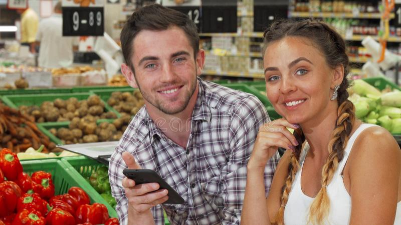 Happy couple smiling to the camera at the groceries store. Beautiful young women and her handsome men using smart phone while picking food to buy at the stock photo
