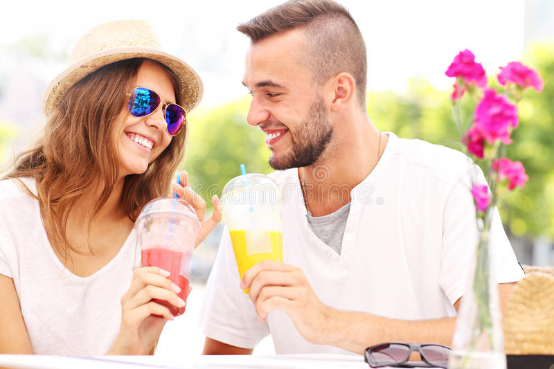 Happy couple and smoothies in a cafe stock images