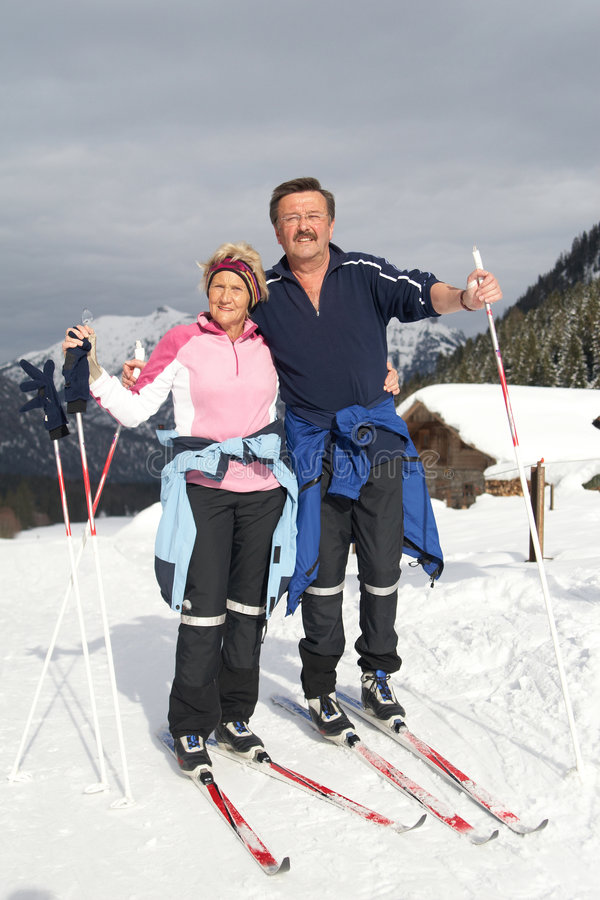 Happy couple in snow. A senior couple outdoor in a winter setting. The active couple is about to go crosscountry skiing royalty free stock images