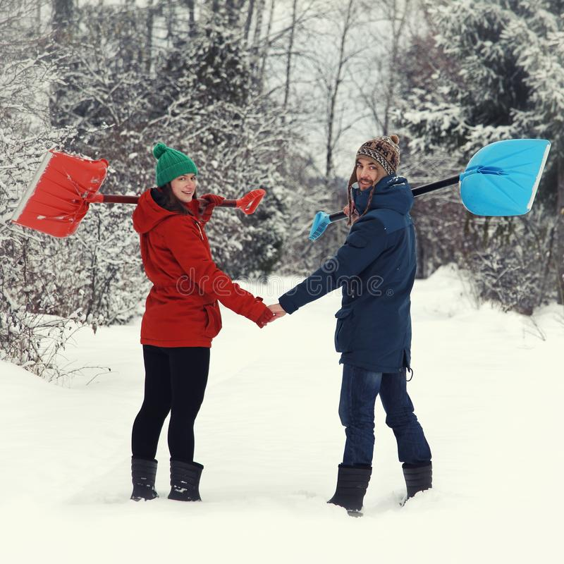 Happy couple with snow shovels. On rural road stock images