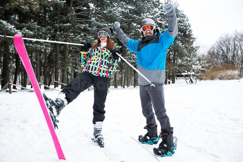 Happy couple of snowboarder and skier having fun stock photo