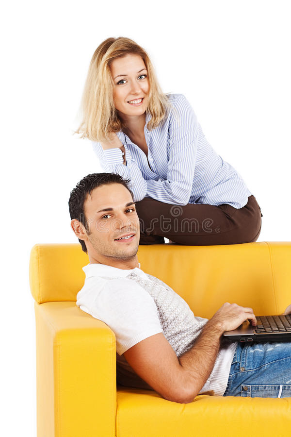 Happy couple on sofa with laptop computer stock image