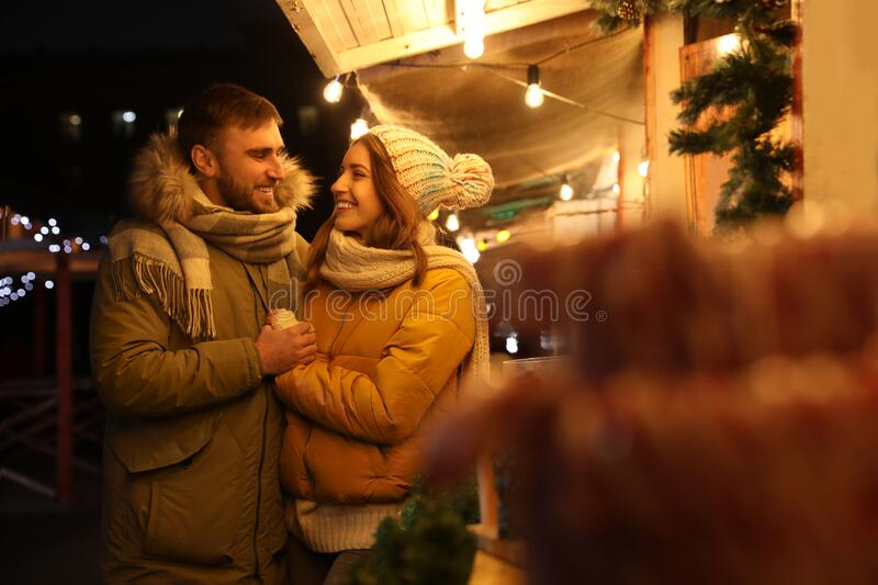 Couple spending time at Christmas fair royalty free stock image