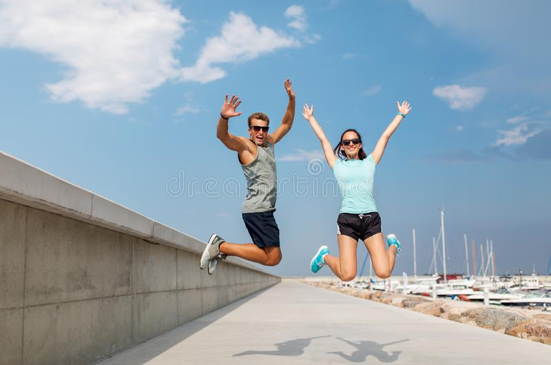 Happy couple in sports clothes jumping on pier. Fitness, sport and lifestyle concept - happy couple in sports clothes jumping on pier royalty free stock image