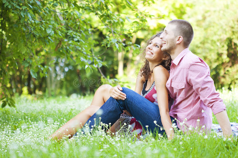 Happy couple in the spring park. Young happy couple sitting on ground enjoying spring in the park stock photography