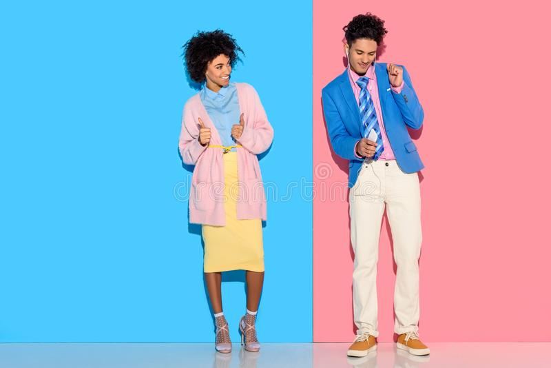 Happy couple standing in distance of each other on pink and blue. Background royalty free stock images