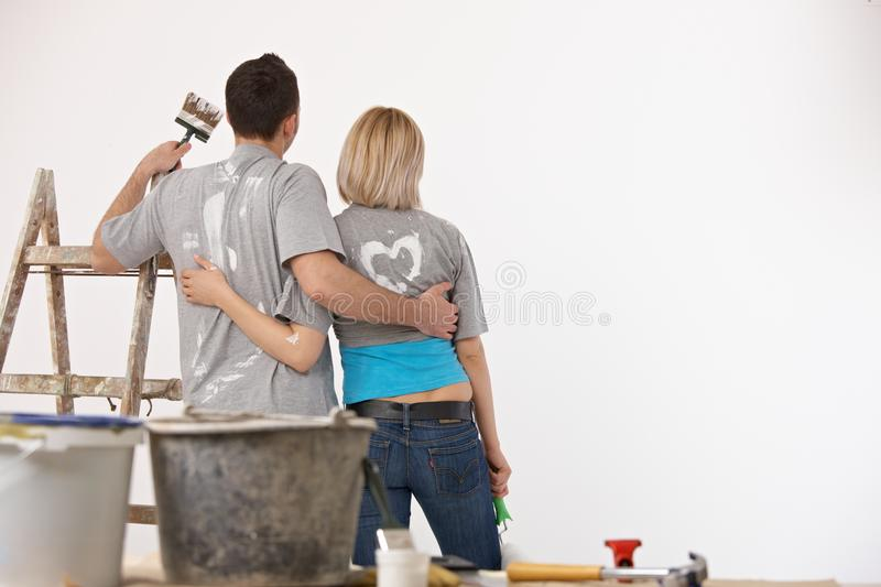Happy couple standing front of painted white wall. Happy casual caucasian couple standing front of painted white wall. Home renovation, new home, indoors. ladder royalty free stock image