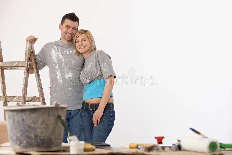 Happy couple standing front of painted white wall royalty free stock photos