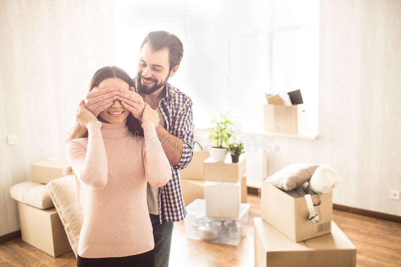 Happy couple are standing inside their new house. Young man has closed eyes to his wife. He prepared surprise for her. Happy couple are standing inside their new royalty free stock image