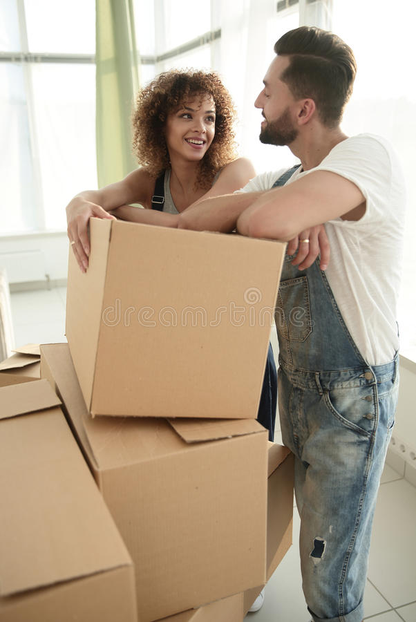 Happy couple standing near boxes in their new apartment. royalty free stock image