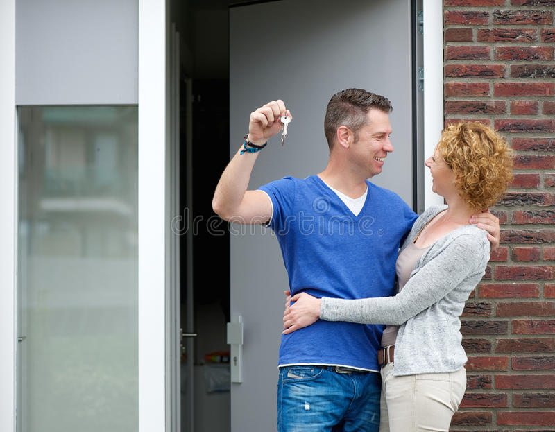 Happy couple standing outside new home with keys. Portrait of a happy couple standing outside new home with keys stock photos