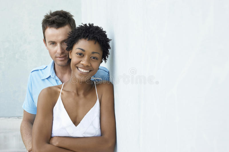 Happy Couple Standing Together Against Wall royalty free stock images